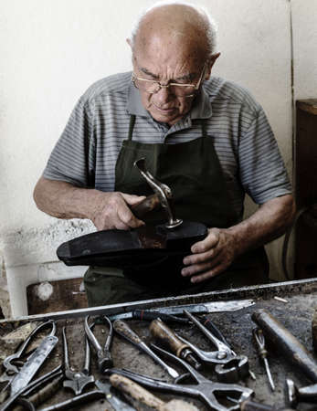 Old shoemaker adjusts the sole of a shoe