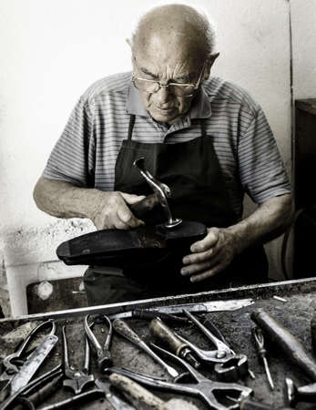 Old shoemaker adjusts the sole of a shoe - Vintage Edition