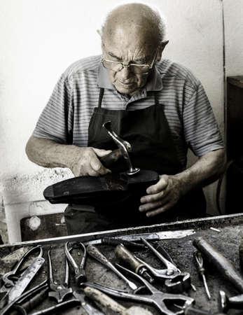 Old shoemaker adjusts the sole of a shoe - Vintage Edition