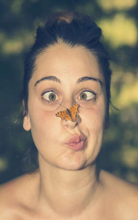 Funny portrait of a girl annoyed by a butterfly on her nose.