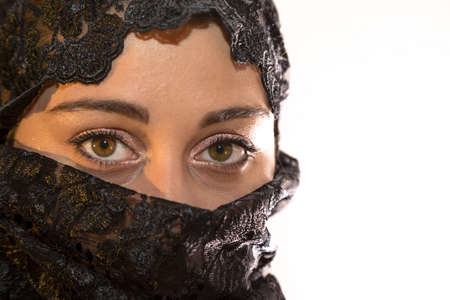 Look of beautiful Mediterranean woman covered with a black veil with empty space for text  Stock Photo