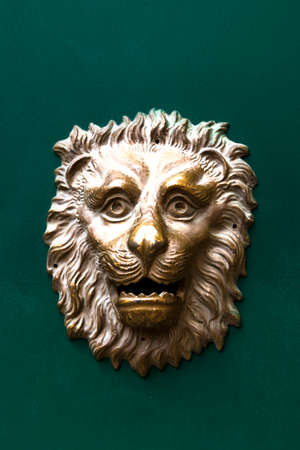 Golden lion mailbox against green wood background photo