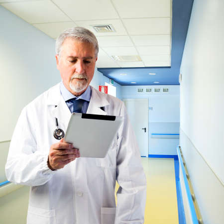 Doctor in the hallway of the hospital with tablet photo