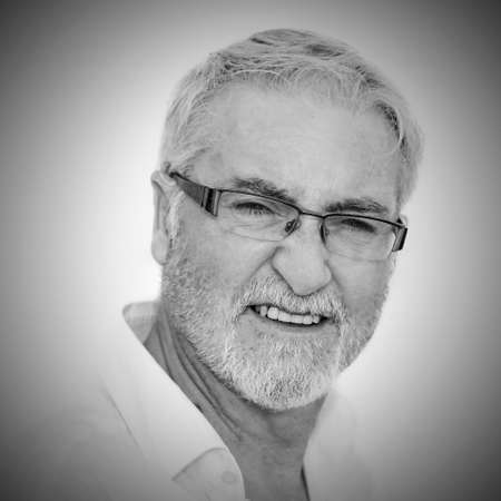 Portrait of senior man against white background photo