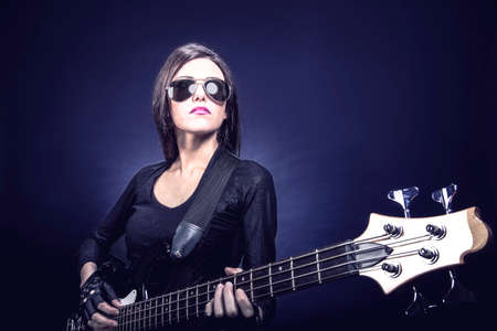 Young brunette woman playing bass against dark blue background, Music concept portrait