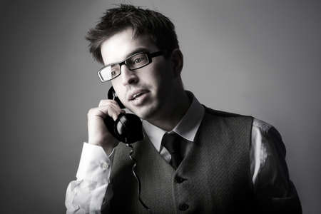 Young smart business man talking on the phone against grey background