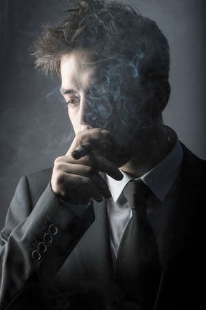 Young stylish man smoking a cigar photo