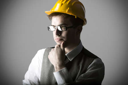 engineer's: Portrait of thoughtful smart young engineer with helmet against grey background Stock Photo