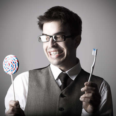 Happy smart young man with a lollipop in one hand and a toothbrush in the other against grey background photo