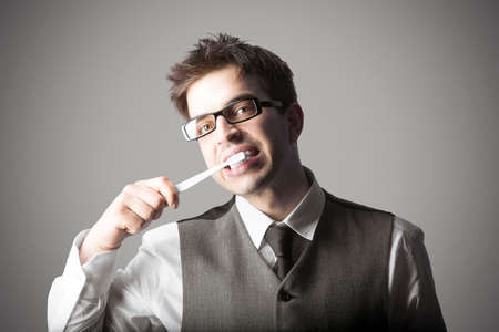 Young stylish man with eyeglasses brushing teeth against grey background