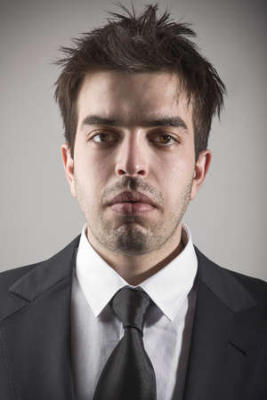 Fashion portrait of young stylish man with a suit and tie against grey background