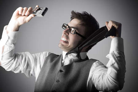 Laughing young man makes a funny and dangerous selfie with a compact camera against grey background