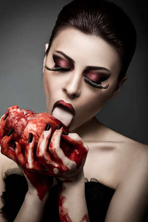Beauty young woman licks blood from human heart against grey background Stock Photo