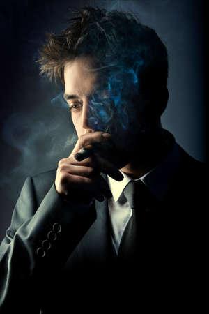 Young handsome stylish man smoking cigar, Fashion portrait photo