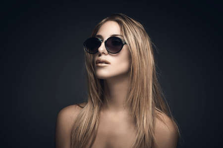 Beauty portrait of sexy blonde woman with sunglasses against grey background photo
