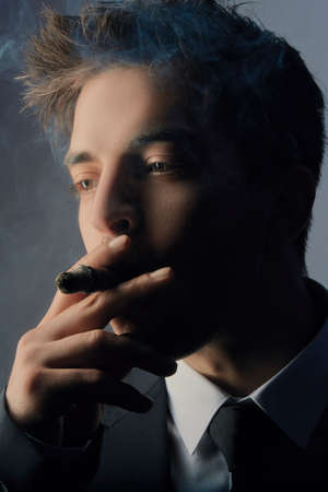 Portrait of handsome stylish young man smoking a cigar