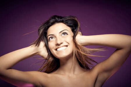 Beauty portrait of young smiling sexy woman against colorful background