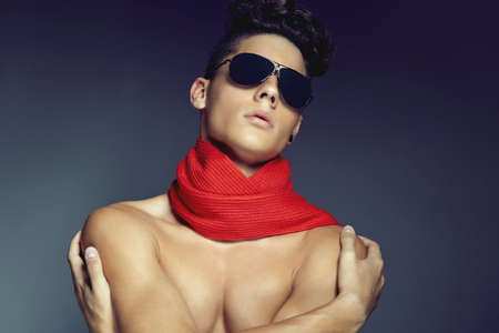 Fashion beauty portrait of young man with sunglasses and scarf against blue background photo