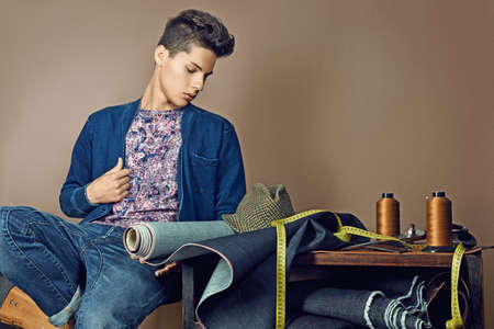 Fashion portrait of handsome young man with tools for sewing denim Stock Photo