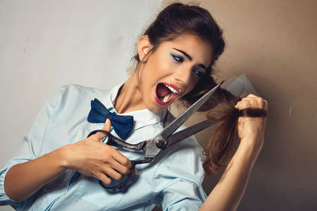 Funny portrait of young sexy woman tries to cut his long hair with a huge scissor
