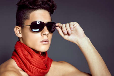 Fashion beauty portrait of sexy young man with sunglasses and scarf against blue background