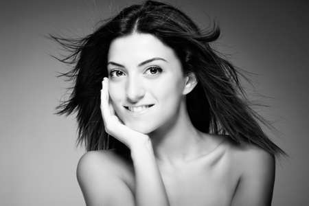 Monochromatic beauty portrait of young sexy woman against grey background