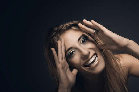Portrait of young smiling sexy woman against blue background with copyspace Stock Photo