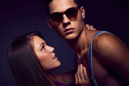 Fashion portrait of young beautiful couple against blue background