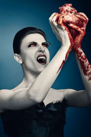 Vampire woman brings up a human heart against grey background