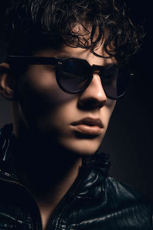 Fashion portrait of sexy young man with sunglasses against dark gray background