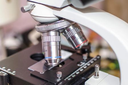 Biopsia: Microscopio de investigación de laboratorio. Vista de primer plano de objetivos y microslide en un escenario Foto de archivo