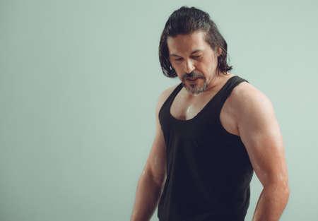 Male bodybuilder wearing dark tanktop on ripped muscular torso in studio shot