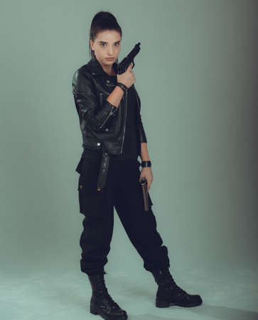 Shot of a military woman posing with guns,in a black jacket