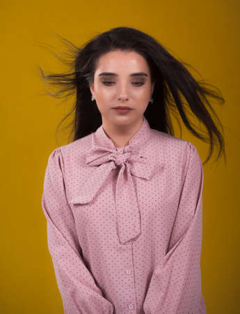 young beautiful brunette model in pink sweater,laughs and shakes his hair in the air,yellow background on the back,caressing looks very sweet camera,posing in studio