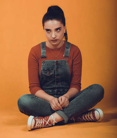beautiful girl model in a red sweater and blue overalls posing,sitting on the floor