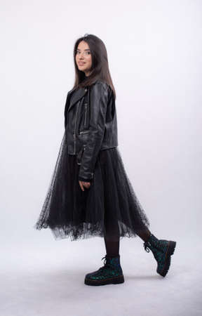 Happy beautiful woman in blue dress posing in studio isolated on white background,black long boots on his feet, Full length portrait,put on a black jacket