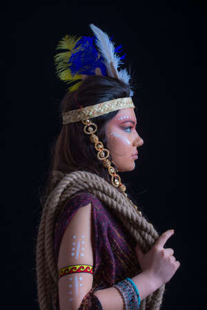 Close up portrait of shamanic female with Indian feather hat and colorful makeup.Native american. Indian woman in traditional dress,