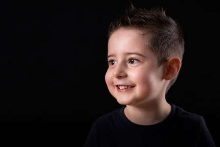 Close up portrait of a young BOY joyful smiling expression, against a black background at home, interior. Foto de archivo