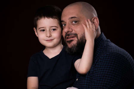 Portrait bearded father and son on black background