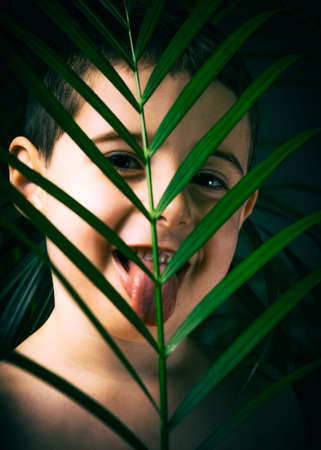 The boy looks at the camera, with palm leaves in the foreground. Childrens portrait through the leaves. 版權商用圖片