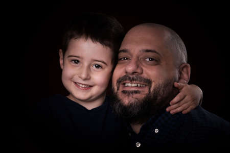 Portrait bearded father and son smile for camera on black background 版權商用圖片