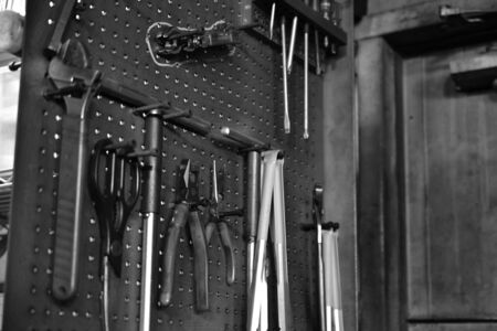 Professional work tools hanging on steel wall as background. Black and White Photo.