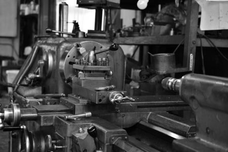 Obsolete lathe at factory. Black-and-white photo.