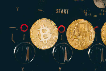 Virtual cryptocurrency money Bitcoin golden coin on Machine controller plates of car part. The future of money. Computational equipment. Blue mother board. Shot directly from above.