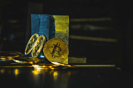 Virtual cryptocurrency money Bitcoin golden coin on metal plates of car part. The future of money. Computational equipment. Blue mother board. Shot directly from above.