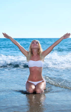 Young Beautiful woman doing relaxation exercises on sand beach photo