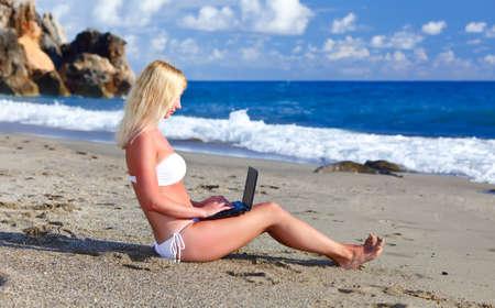 Sexy beautiful woman in bikini using laptop at the beach photo