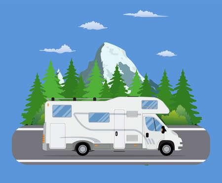 Road travel trailer driving on forest area road.