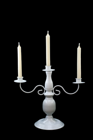 white candlestick with three burning white candles in front of black background photo