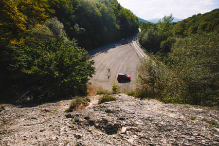 eminence: Jumping man, standing next to a red car. Shot from above Stock Photo